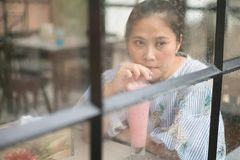 Woman in coffee shop sitting at the glass wall on a rainy day an royalty free stock photos
