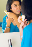 Asian woman combing hair in bathroom mirror Stock Photography
