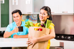 Asian woman coming home from grocery shopping Stock Photos