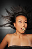 Asian woman with a condom in her mouth Royalty Free Stock Photos