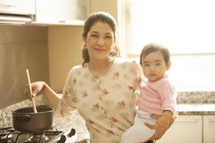Asian woman cooking with baby. Asian women cooking with baby in kitchen Royalty Free Stock Photo