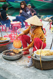 Asian woman cooking chicken paws in street market in Vietnam Royalty Free Stock Image