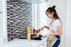 Asian woman cooking spaghetti in kitchen happily. People and lifestyles concept. Food and drink theme. Interior decoration and ho. Usework theme stock images