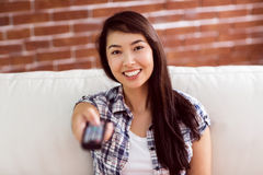 Asian woman on the couch changing channel Royalty Free Stock Images