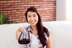 Asian woman on the couch changing channel Royalty Free Stock Photo