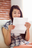 Asian woman on the couch reading letter Royalty Free Stock Image