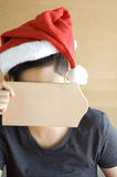 Asian woman cover her face with blank board. Asian woman wear santa hat cover her face with blank wooden board with copyspace for text Stock Photos