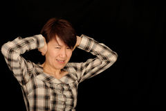 Asian woman covering ears. Half body portrait of middle aged Asian woman covering ears with anguished expression Stock Photography