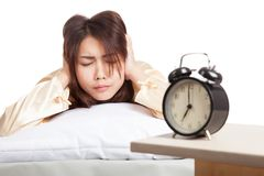 Asian woman covering ears with hands and alarm clock Royalty Free Stock Images