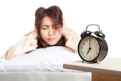 Asian woman covering ears with hands focus at alarm clock. Isolated on white background Stock Images