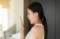 Asian woman covering her mouth and smell her breath with hands upter wake up,Bad smell. Selective focus royalty free stock image
