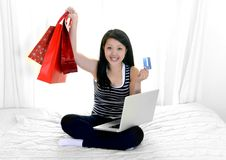 Asian woman with credit card and shopping bags Stock Images