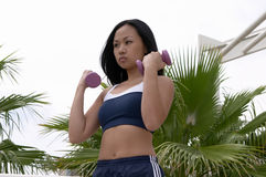 Asian Woman Curling Two Purple Dumbbells Stock Image