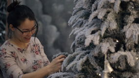 Asian woman decorates Christmas tree, speaks, smiles indoors stock footage