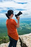 Asian woman with digital camera, outdoor at the daytime on summe. Asian woman with digital camera at view point on the top of mountain, travel on vacation. Back Royalty Free Stock Photos