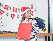 Asian woman disappointed about payment when buy a lot of christm. As gift in shopping bags,upset expenses after shopping time,unhappy girl poor shopaholic Royalty Free Stock Photo