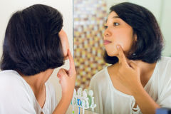 Asian woman discovering a pimple Royalty Free Stock Images