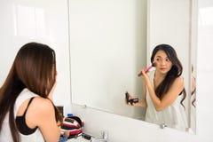 Asian woman do cosmetic powder brush. Asian woman with fresh skin with cosmetic powder brush at mirror. Base for perfect make-up. Applying make up. Beauty royalty free stock photo
