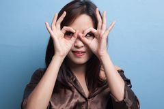 Asian woman do funny  double OK sign as glasses. Royalty Free Stock Image