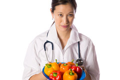 Asian woman doctor offering bowl of peppers Stock Image