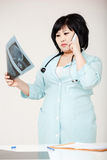 Asian woman doctor in robe discussing diagnosis talking on phone, considering X-ray picture. Medical mistake, the Royalty Free Stock Image