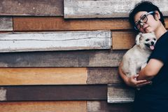 Asian woman hugging dog so cute with wooden wall stock image