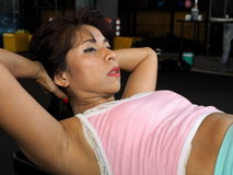 Asian woman doing abdominal crunches Royalty Free Stock Photo