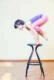 Asian woman doing exercise or yoga at home at chair Royalty Free Stock Image