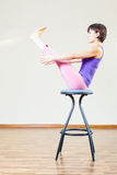 Asian woman doing exercise or yoga at home at chair Stock Image