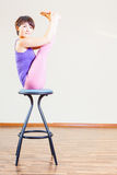 Asian woman doing exercise or yoga at home at chair Royalty Free Stock Images