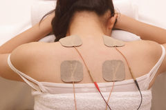 Asian woman is doing massage of electrical -stimulation ( TENs ) Stock Photos