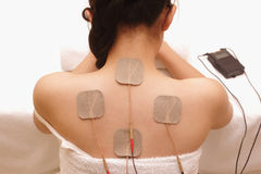 Asian woman is doing massage of electrical -stimulation ( TENs ) royalty free stock photography
