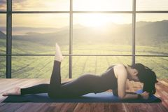 Asian woman doing plank exercise at home. Picture of Asian woman doing plank exercise at home with landscape on the window royalty free stock images