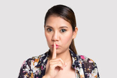 Asian woman doing silence sign against. On white background Royalty Free Stock Photos