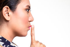 Asian woman doing silence sign against Stock Photo