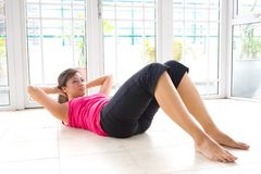 Asian woman doing sit ups. Young Asian woman doing sit ups to strengthen stomach muscle in calm home environment Stock Images