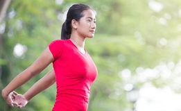 Asian woman doing stretching exercise during outdoor cross train. A portrait of a asian woman doing stretching exercise during outdoor cross training workout stock photography