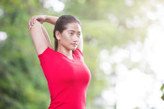 Asian woman doing stretching exercise during outdoor cross train. A portrait of a asian woman doing stretching exercise during outdoor cross training workout royalty free stock photo