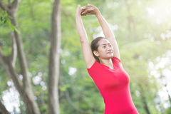 Asian woman doing stretching exercise during outdoor cross train Royalty Free Stock Photos