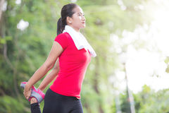 Asian woman doing stretching exercise during outdoor cross train. A portrait of a asian woman doing stretching exercise during outdoor cross training workout royalty free stock image
