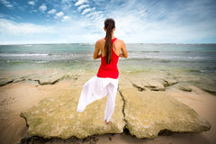 Asian woman doing yoga on beach Stock Images