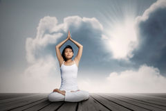 Asian woman doing yoga exercise under blue sky Stock Photography