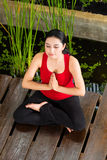 Asian woman doing yoga in tropical setting Royalty Free Stock Image