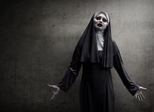 Asian woman dressed in evil nun. Standing in front of wall Royalty Free Stock Photography