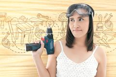 Asian woman dressed in white top holding a cordless electric dri. Ll on wood background Stock Images
