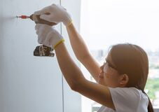 Free Asian Woman Drilling Screw Into Apartment Wall With Cordless Drill. Woman Wear Safety Glasses And Hand Holding Drilling Tool For Stock Images - 197664694