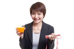 Asian woman drink orange juice hold measuring tape. Stock Photo