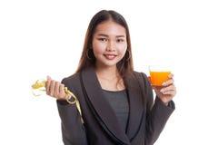 Asian woman drink orange juice hold measuring tape. Royalty Free Stock Image