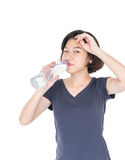 Asian woman drinking bottled water. Young asian woman drinking bottled water isolated on white background Royalty Free Stock Image