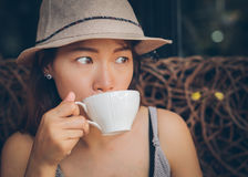 Asian woman drinking a coffee. Asian woman drinking a cup of coffee. Vintage retro style photo with color filters, vignette effect, and some fine film noise Stock Photo